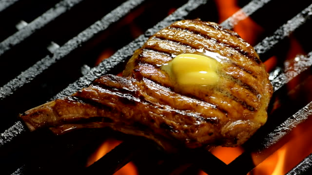 Grilled pork chop with butter on the top on Barbecue grill - slow motion video