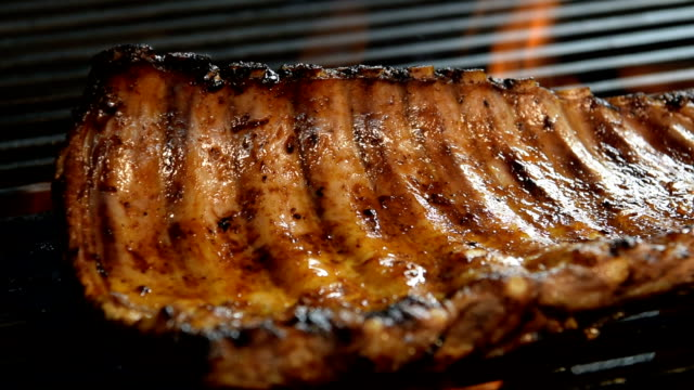 Grilled pork ribs on the flaming grill - slow motion