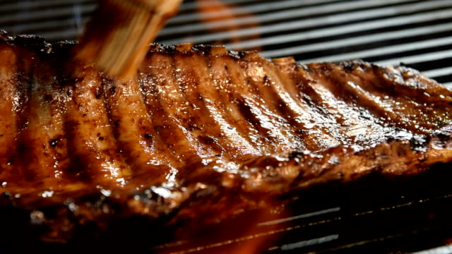 Grilled pork ribs with Barbecue sauce on the flaming grill - slow motion video