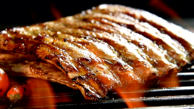 vídeos de stock e filmes b-roll de grilled pork ribs/steak on the flaming grilled - slow motion - costeleta comida