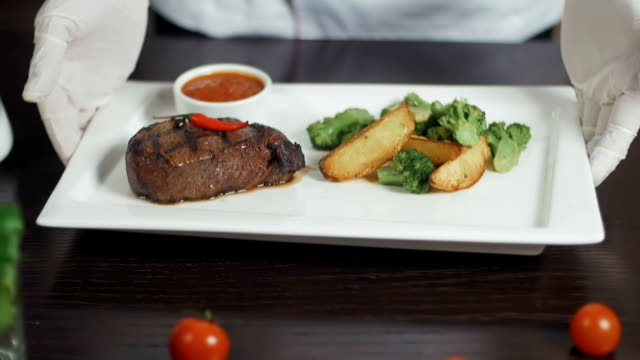 Grilled red beef pork meat barbecue steak fillet with broccoli and potato served on white rectangular plate video