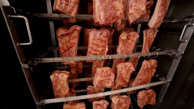Grilled ribs, meat products at a smokehouse rack in a food factory. Grilled ribs, meat products at a smokehouse rack in a food factory. HD. smokehouse stock videos & royalty-free footage