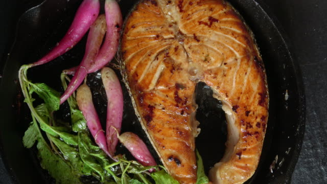 grilled salmon fillet with roasted organic radishes - тарелки стоковые видео и кадры b-roll