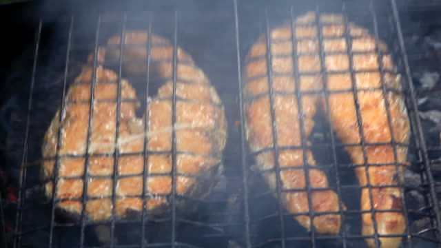 Grilled salmon fish steaks rotating - Closeup of barbecue grill video