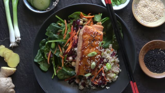 grilled salmon on a spinach salad with quinoa, carrots, cranberries, chickpeas, edemame, pumpkin seeds, and a ginger miso dressing. - тарелки стоковые видео и кадры b-roll