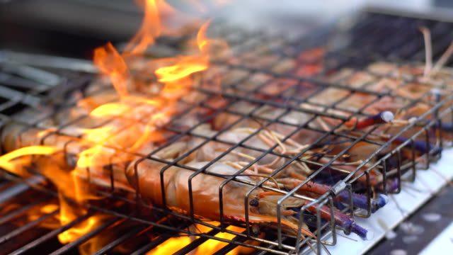 Grilled seafood on hot pan with smoke. Selective focus and free space for text. Healthy food concept.