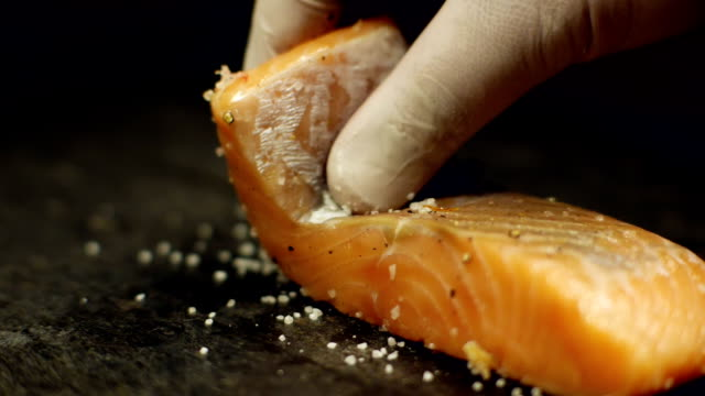 stockvideo's en b-roll-footage met gegrilde steaks zalm, chef-kok in de keuken van restaurant - vis en zeevruchten