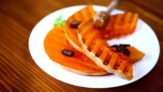 grilled sweet ripe pumpkin, in a plate with honey - zucchini video stock e b–roll