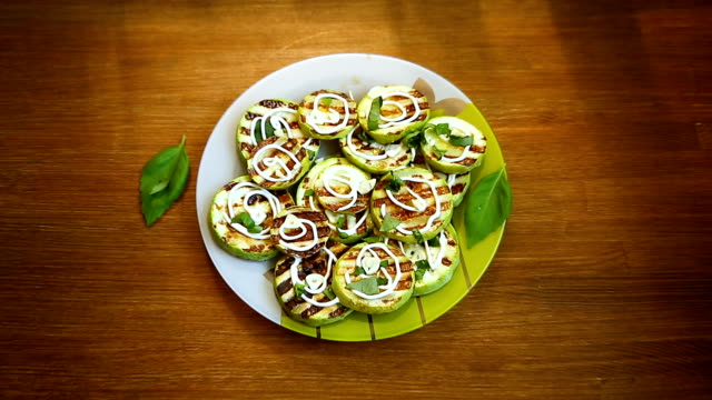 vídeos de stock e filmes b-roll de grilled zucchini slices with garlic and spices - top view, dark wood table, empty
