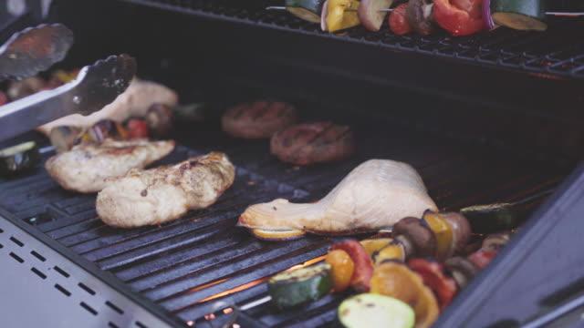 Grilling an Atlantic salmon, chicken breast, vegetable skewers, and vegetarian burgers Grilling an Atlantic salmon, chicken breast, vegetable skewers, and vegetarian burgers on an outdoor grill. skewer stock videos & royalty-free footage