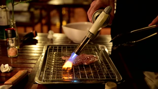 grilling beef slice with fire canned gas on the table - pinze attrezzo manuale video stock e b–roll
