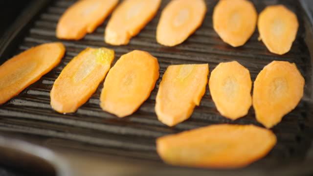 grilling carrot on griddle pan at home kitchen - płyta do pieczenia filmów i materiałów b-roll