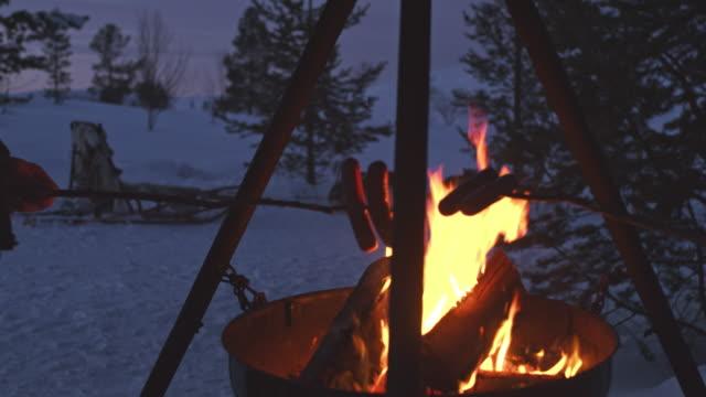 vídeos de stock e filmes b-roll de ms grilling sausages by a campfire in norway - países nórdicos