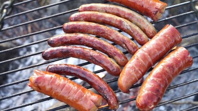 Grilling sausages on barbecue grill video