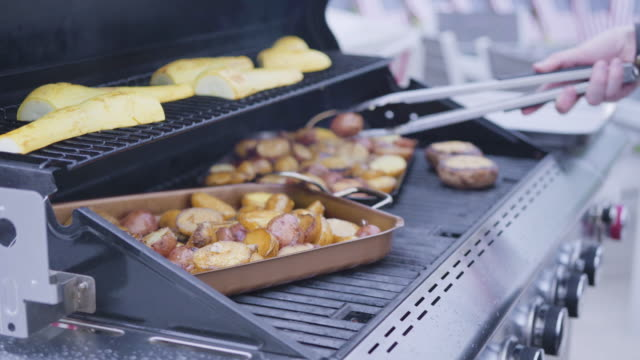 Grilling small potatoes with slices of garlic on an outdoor gas grill.