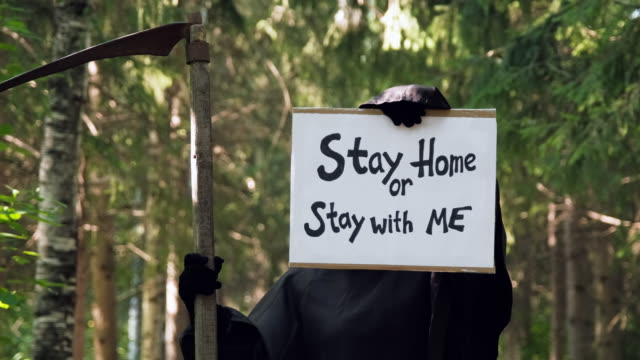 Grim Reaper Shows Sign Stay Home or Stay with Me Scary Looking Grim Reaper Showing Cardboard Sign Stay Home or Stay with Me Outdoors. Slow Motion. Healthcare and Sickness Prevention from Covid19 Coronavirus, Safety and Pandemic Concept halloween covid stock videos & royalty-free footage