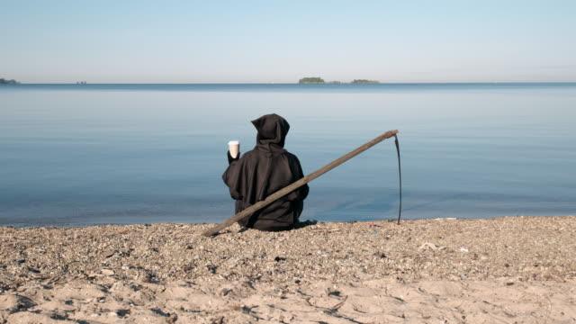 grim reaper sitter vid sjön med kopp kaffe - coffe with death bildbanksvideor och videomaterial från bakom kulisserna