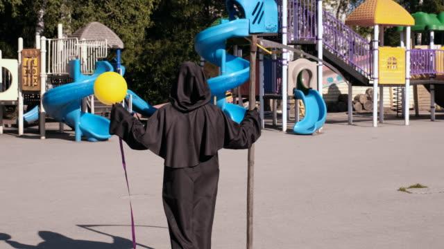 grim reaper con palloncino che cammina lungo il parco giochi - inferno video stock e b–roll