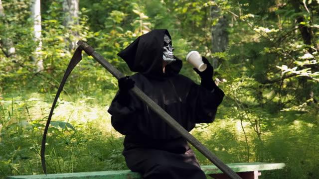 liemannen med scythe drinking coffee i en park - coffe with death bildbanksvideor och videomaterial från bakom kulisserna