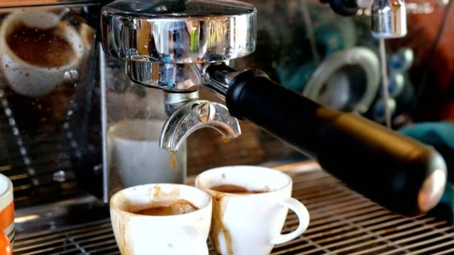 kaffeemühle espresso mit großen kaffeemaschine auf tasse gießen - grind stock-videos und b-roll-filmmaterial