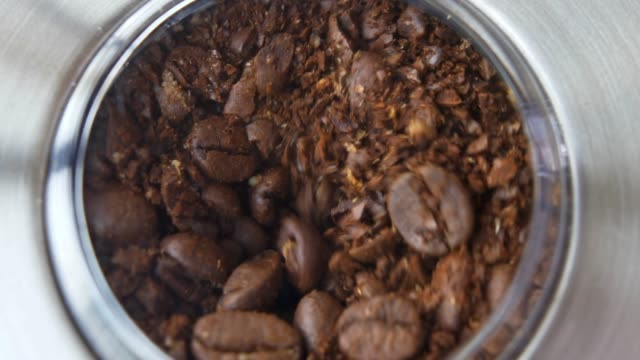 grinding coffee beans in electric grinder close-up slow motion - grindare video stock e b–roll