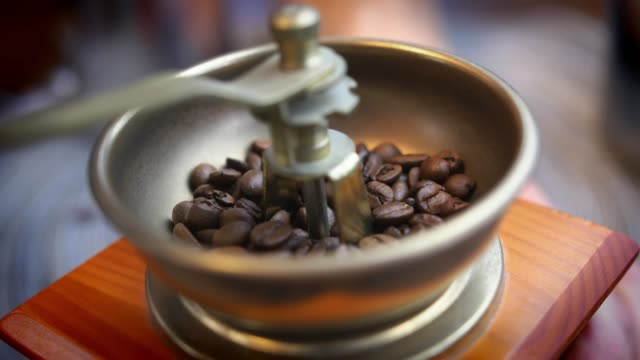 grinding coffee beans in old manual grinder close-up slow motion - grindare video stock e b–roll