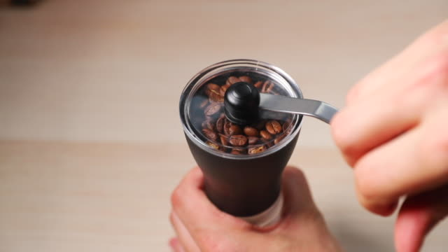 grinding coffee in a handheld grinder when hand-gripping and grinding on a table with a handheld grinder on the side captured in slow motion at 120 fps. - grindare video stock e b–roll