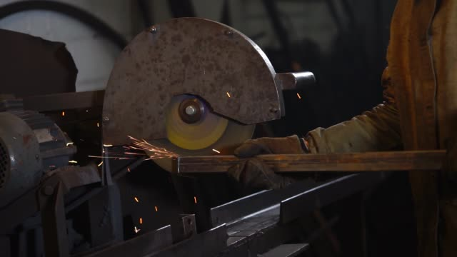 Grinding on edges of metal tube Industrial worker is using big grinding machine to smooth edges of a metal tube. Sparks are popping off the metal tube. handbook stock videos & royalty-free footage