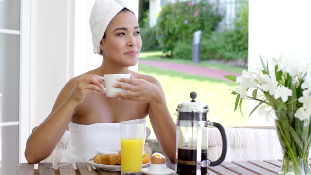 Grinning woman at breakfast table outdoors Grinning beautiful young woman wrapped in white towel at breakfast table with orange juice  pastry  coffee and bouquet outdoors wearing a towel stock videos & royalty-free footage