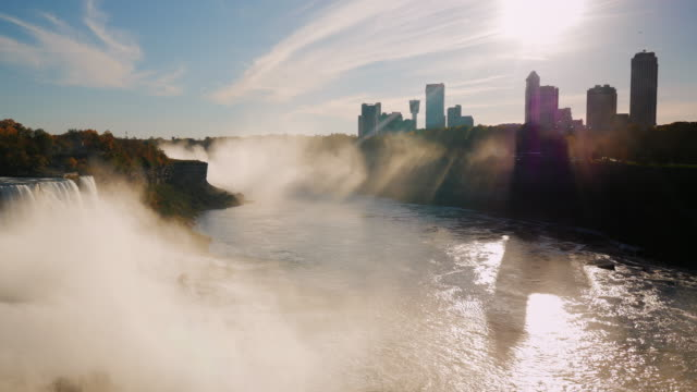 Gripping show - Sunset at Niagara Falls. The rays of the setting sun shines through the skyscrapers on the Canadian shore. Pan shot video