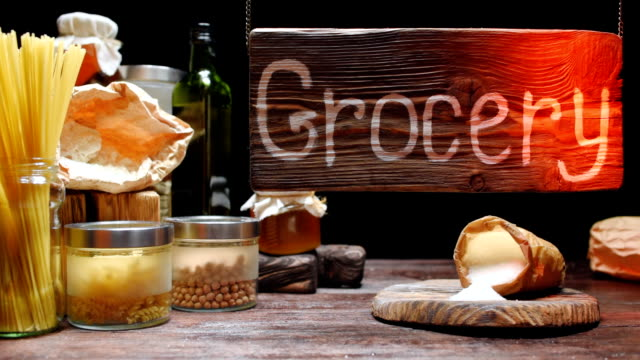 Groceries shop showcase Showcase of homelike dry groceries shop. Beamlight moving over wooden sign board. Various sorts of pasta, flour and sugar, oil and nuts on wooden counter pantry stock videos & royalty-free footage