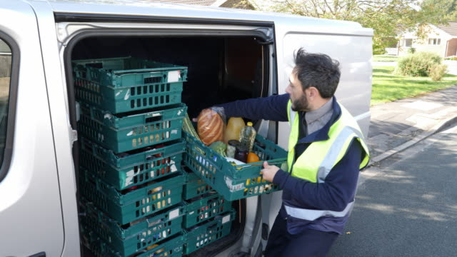 4K: Grocery delivery driver from Supermarket lifts crate of food out of the van Stock 4K video clip footage of a Supermarket delivery van driver who is lifting an online shopping order of food and groceries in a green crate out of his van. The camera moves from low to high whilst he smiles at the camera. food stock videos & royalty-free footage