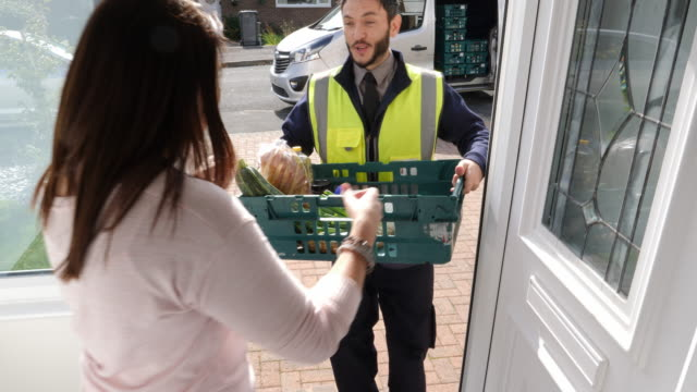 4k: grocery delivery man from supermarket delivers online shopping food order to a woman at her house - food delivery filmów i materiałów b-roll