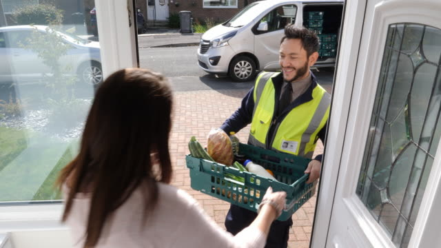 4k: grocery delivery man from supermarket delivers online shopping food order to front door of home - food delivery filmów i materiałów b-roll