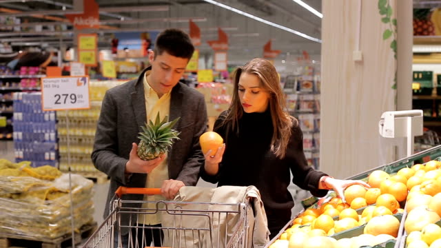 Grocery shopping in two Young couple is grocery shopping at a supermarket aisle buying fruits. snack aisle stock videos & royalty-free footage