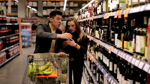 Grocery shopping in two Young couple is grocery shopping at a supermarket aisle buying fruit and wine. snack aisle stock videos & royalty-free footage