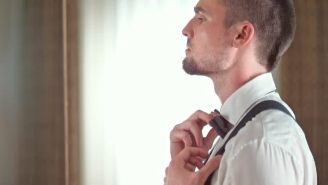 TU Groom adjusting his suspenders and a bow tie