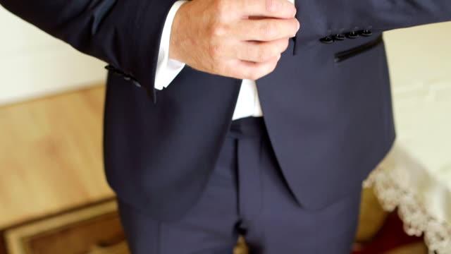 groom adjusting sleeves during wedding - manica video stock e b–roll