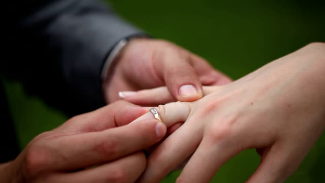 Groom and bride dress each other wedding rings. Close up video