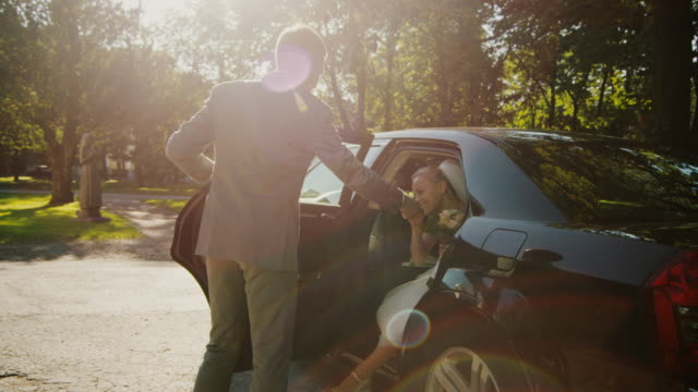 Groom helps bride to get out of the wedding car.