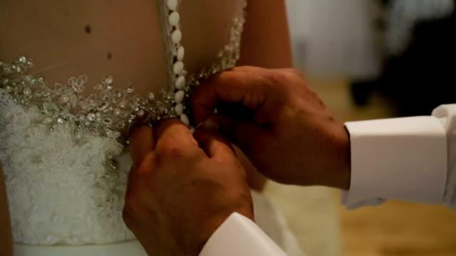 Groom helps his bride to get dressed video