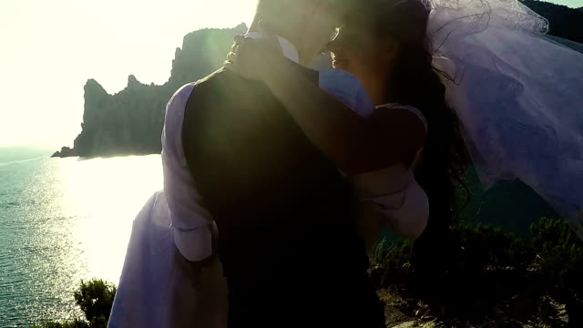 groom holds his bride in his arms video