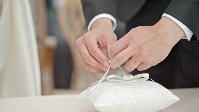 SLO MO Groom placing ring on bride's finger video
