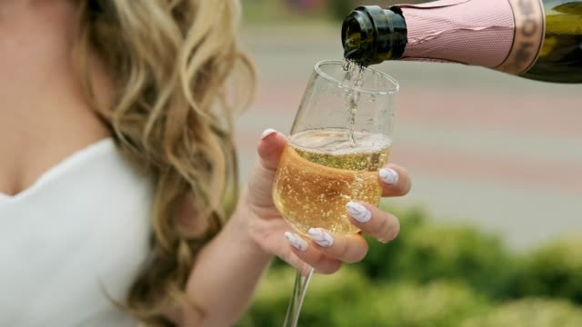 Groom pouring glass of champagne outdoors. Bride and groom having champagne