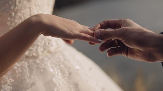 新郎は花嫁の指に婚約指輪を置きます。結婚式のカップル - 指輪点の映像素材/bロール