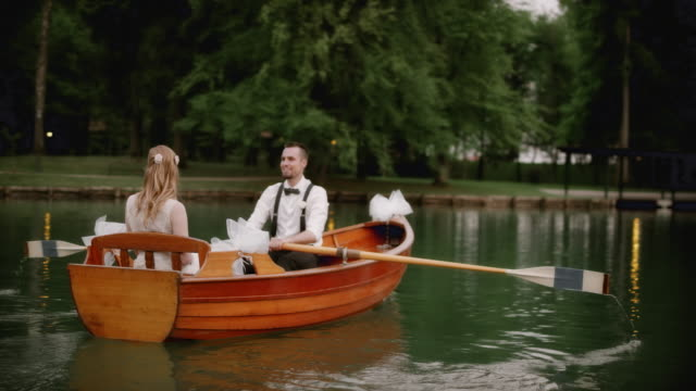 Groom rowing a boat with his bride on a lake video