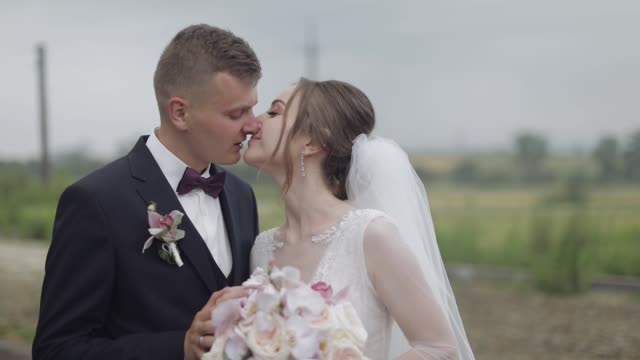 groom with bride making a kiss. wedding couple. happy family. newlyweds - figura femminile video stock e b–roll