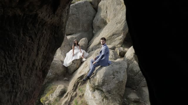 groom with bride sit on a high slope of the mountain. wedding couple. happy - rappresentazione umana video stock e b–roll