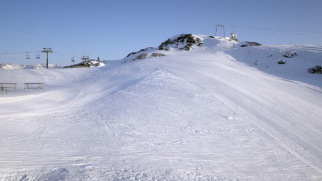 AERIAL Groomed sunlit morning ski runs on mountain top
