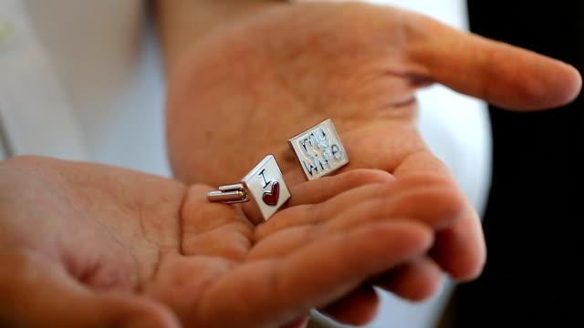Groom's cuff links on hand. video